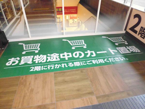 スーパーマーケットのエスカレーター前カート置き場表示