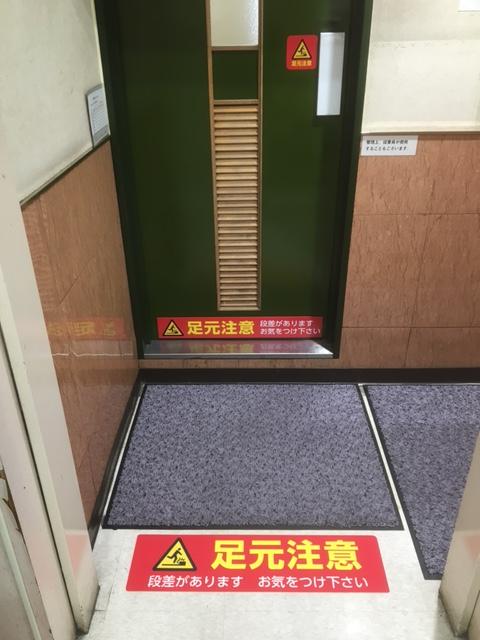 スーパーマーケットのトイレ足元注意床面標示