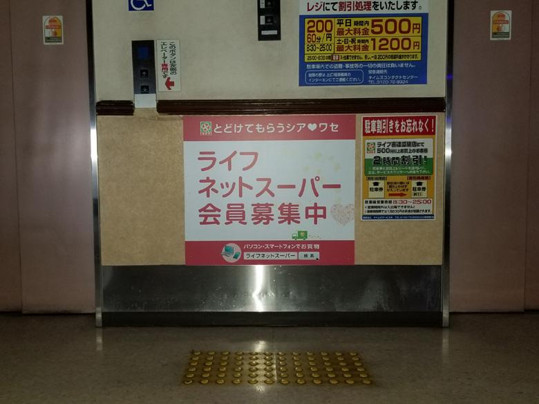 エレベーターボタン下壁面に貼り込んだ新サービス告知シート