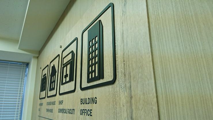 木目調の壁とマッチして上品な仕上がりの社名看板