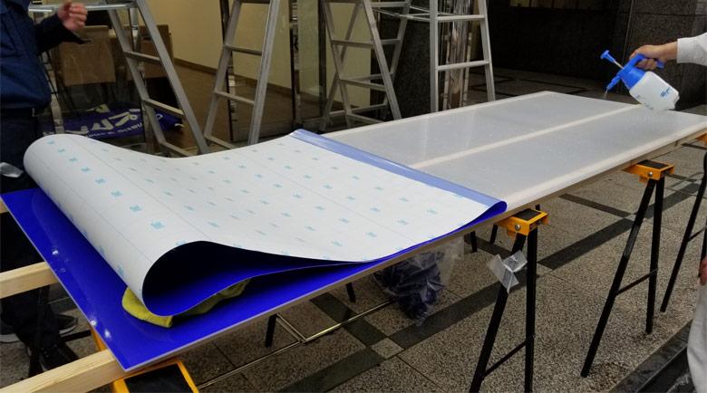 電飾看板の板面を剥がし、新しいデザインのものを丁寧に貼り込んでいきます